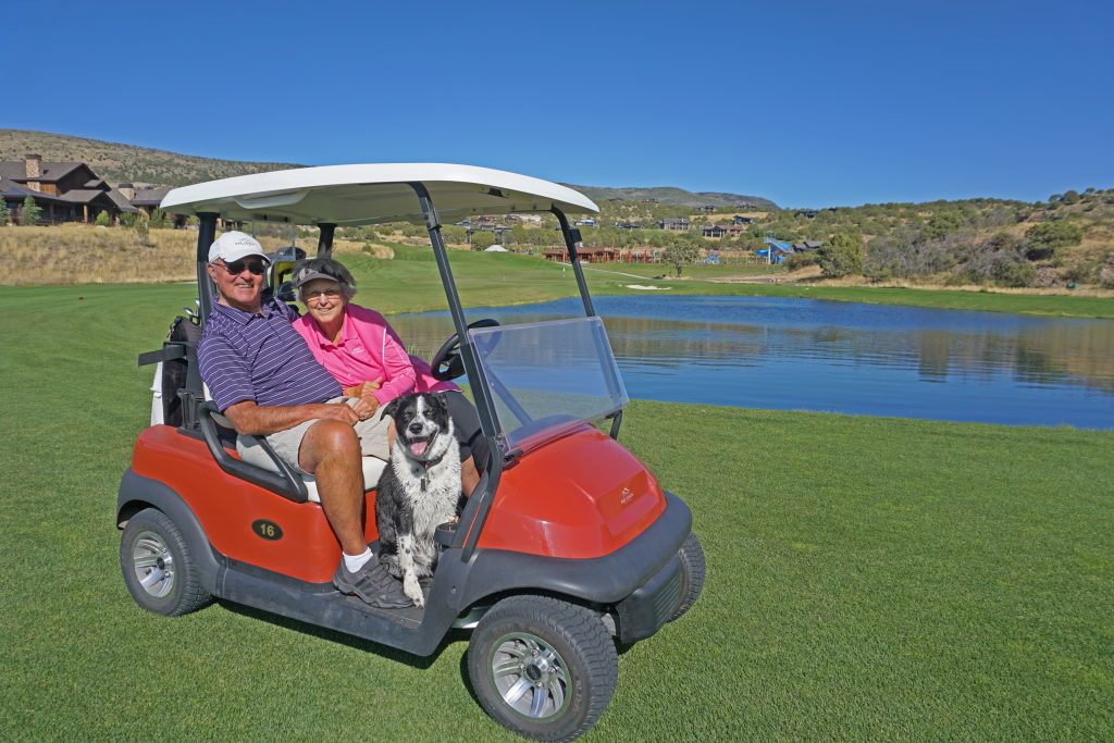 Man and woman on golf cart with a dog